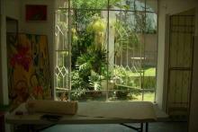 Salón con iluminación y vista a áreas verdes.